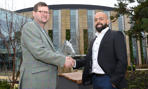 photo of John Mackenzie of Roslin Innovation Centre and Jaymin Amin of Ingenza shaking hands outside Roslin Innovation Centre